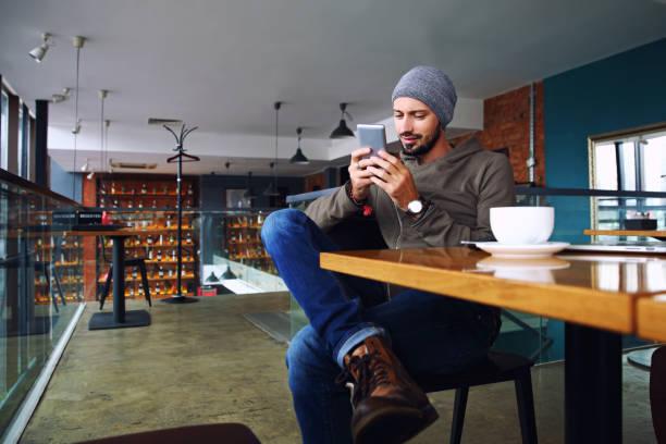 junge hübsche hipster mann mit bart sms mit seinem mobiltelefon an der bar und mit einem cappuccino - möbel 24 online stock-fotos und bilder