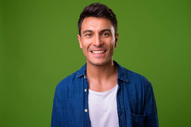 jonge knappe man van de hispanic tegen groene achtergrond - green screen stockfoto's en -beelden