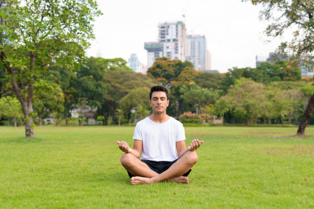 Young handsome Hispanic man meditating at the park stock photo