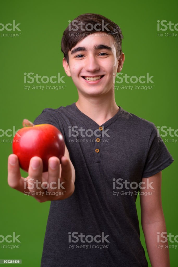 Young handsome Iranian teenage boy against green background royalty-free stock photo