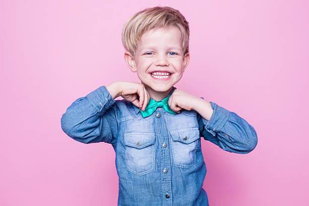 junge schöne lächelnd kind mit blauen hemd und krawatte mit schmetterling - kleinkind frisur stock-fotos und bilder