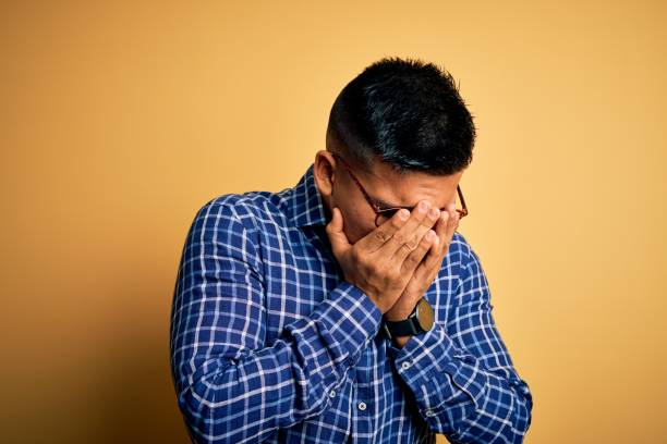 joven hombre latino guapo con camisa casual y gafas sobre fondo amarillo con expresión triste cubriendo la cara con las manos mientras llora. concepto de depresión. - vergüenza fotografías e imágenes de stock