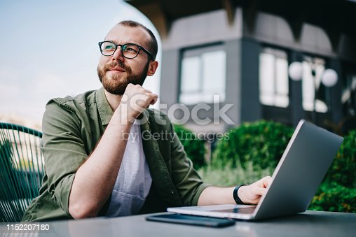 Young handsome male 20 years old in eyeglasses sitting at street cafe during free time with new modern laptop, bearded man freelancer  thoughtfully looking aside and thinking about distance work