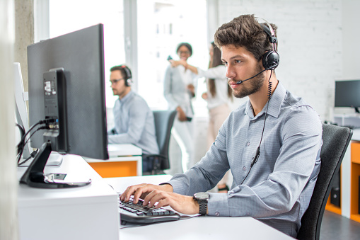 istock Young handsome male customer support phone operator with headset working in call center. 854480672