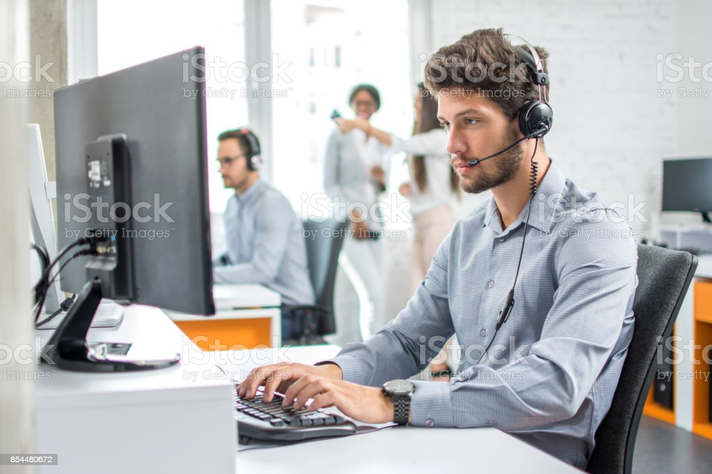 Young handsome male customer support phone operator with headset working in call center. stock photo