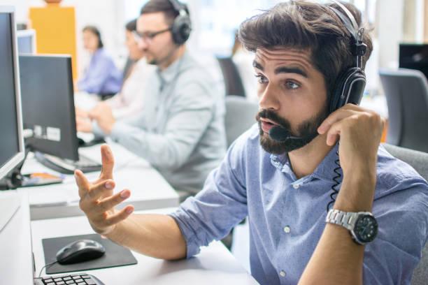Junge stattliche männliche technische Support-Agent versucht, etwas zu erklären, während der Arbeit am Computer im Callcenter – Foto