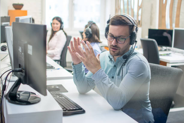 Young handsome male technical support agent trying to explain something to a client while using hands-free headset at call center stock photo