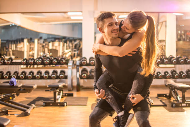 Young handsome man carrying on his girlfriend piggyback in the gym. stock photo