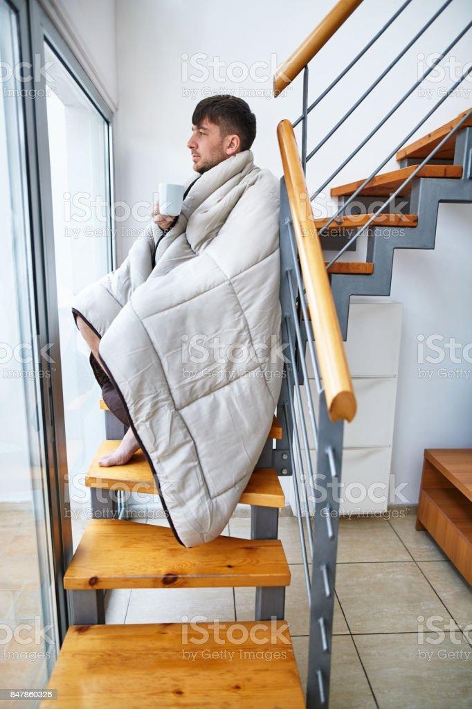 Schöner junger Mann bedeckt mit Decke heißen Kaffee trinken sitzen auf Treppen – Foto