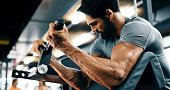 istock Young handsome man doing exercises in gym 876874020