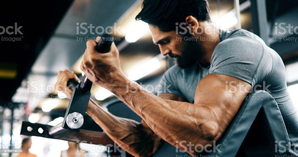 Jeune homme beau faire des exercices dans la salle de gym - Photo
