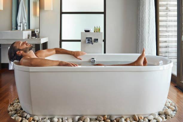 schönen jungen Mann in der Badewanne genießen – Foto