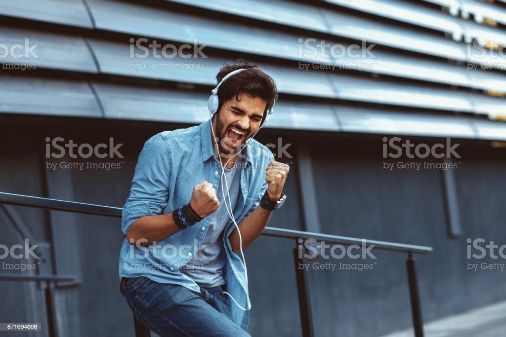 Young handsome man enjoying music via headphones stock photo