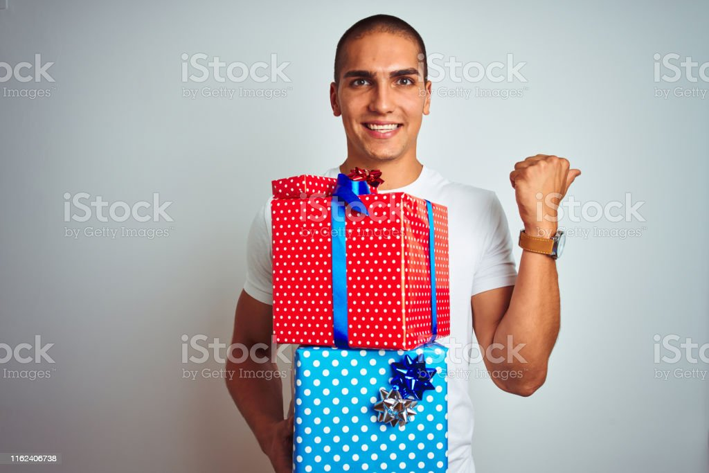 Young handsome man holding birthday gifts over white isolated...