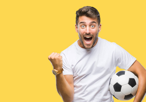 young handsome man holding soccer football ball over isolated background screaming proud and celebrating victory and success very excited, cheering emotion - soccer supporter portrait imagens e fotografias de stock