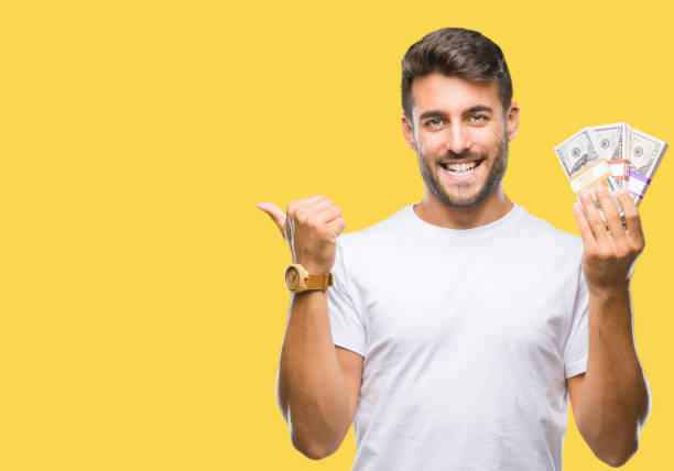 young handsome man holding stack of dollars over isolated background pointing and showing with thumb up to the side with happy face smiling - dollar bill стоковые фото и изображения