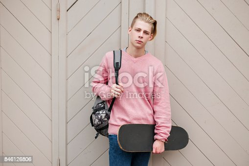 846124694 istock photo young handsome man in a pink sweater with a skateboard and a backpack near a wooden wall 846126806