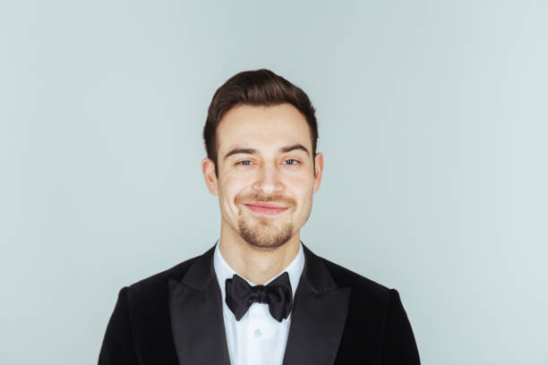 young handsome man in a tuxedo,  looking at the camera - tuxedo stock photos and pictures