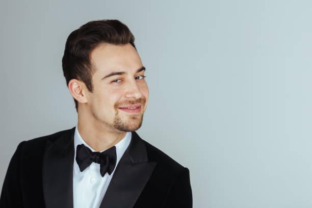 young handsome man in a tuxedo,  looking at the camera - seduzione foto e immagini stock