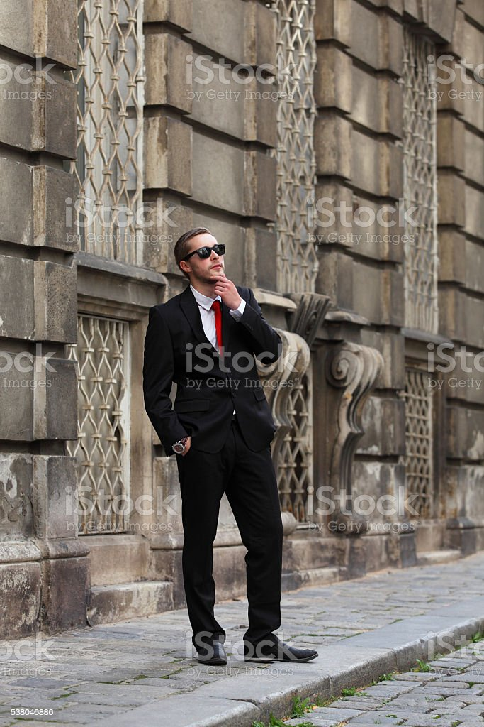 9aea3da74e72 Young handsome man in black suit with red tie royalty-free stock photo