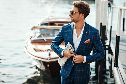 Young handsome man in classic suit over the blurred lake buttoning his jacket
