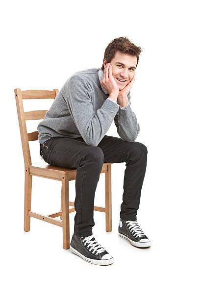 若いハンサムな男の灰色のセーターの椅子に座る ストックフォト