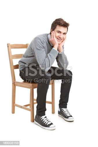 Jeune bel homme dans un pull gris assis sur une chaise for Abdos assis sur une chaise