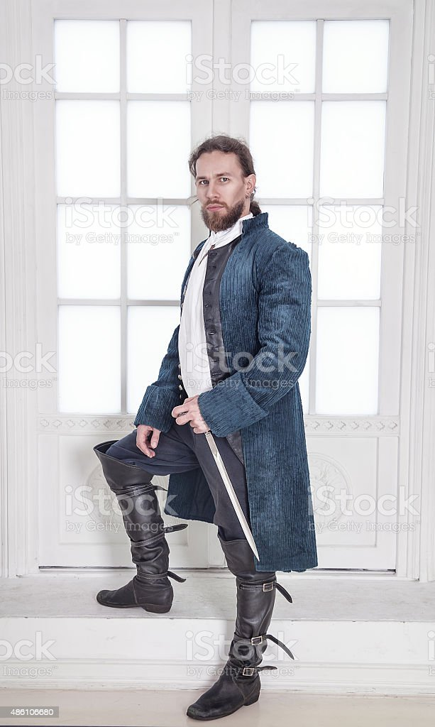 Young handsome man in medieval clothes with sword standing stock photo