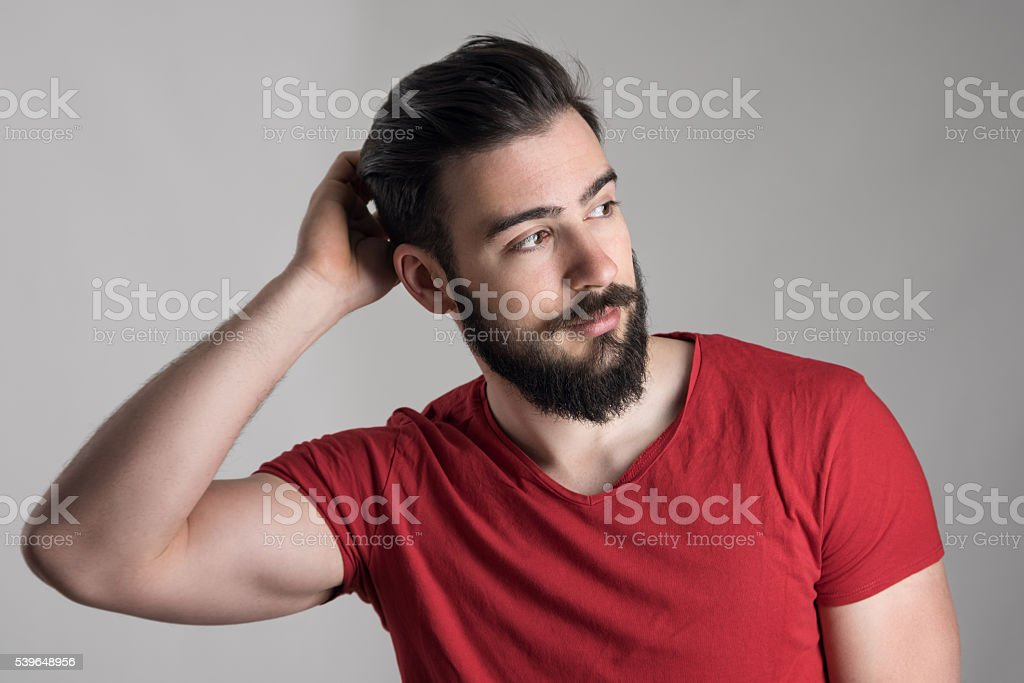 Young handsome man in red t-shirt scratching head looking away stock photo