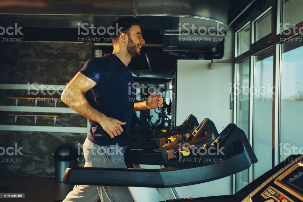 Young handsome man in sportswear running on treadmill at gym stock photo