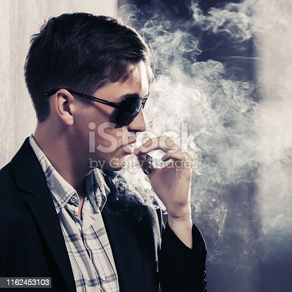 907934274 istock photo Young handsome man in sunglasses smoking a cigarette on city street 1162453103
