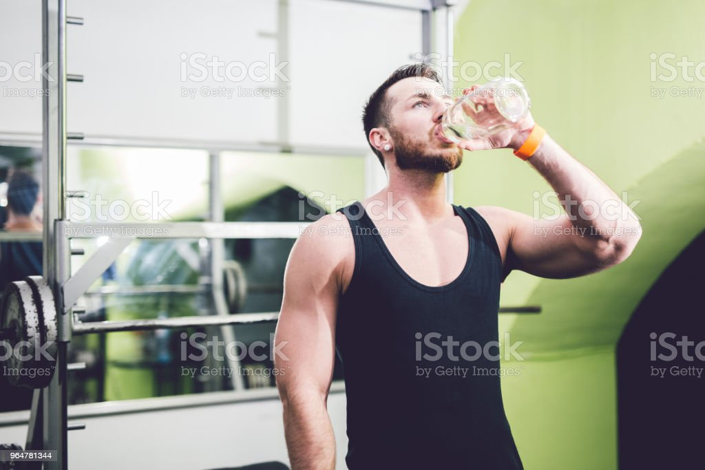 Young handsome man in the gym is drinking water. royalty-free stock photo