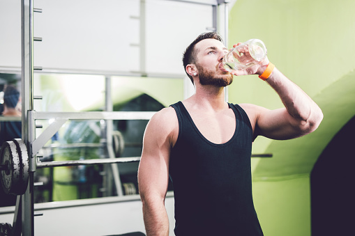 Young Handsome Man In The Gym Is Drinking Water Stock Photo - Download Image Now