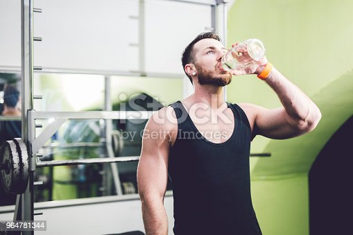 Young Handsome Man In The Gym Is Drinking Water Stock Photo & More Pictures of 20-29 Years