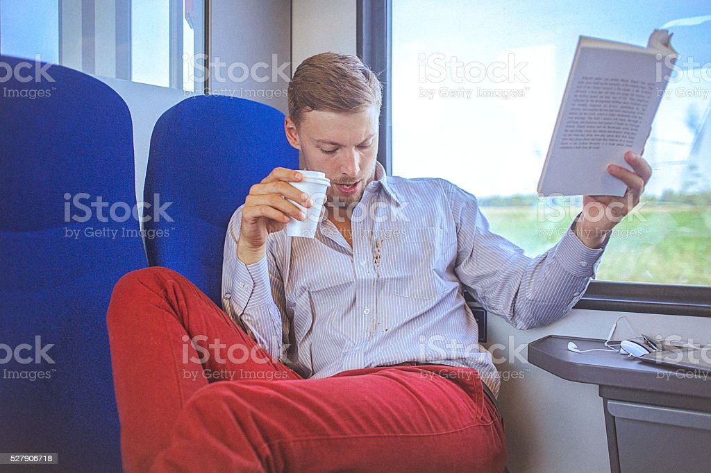 Young handsome man in train spilling coffee on shirt stock photo