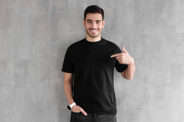 young handsome man isolated on gray textured wall, smiling while pointing with index finger to black t-shirt, copyspace for advertising - one man only stock pictures, royalty-free photos & images