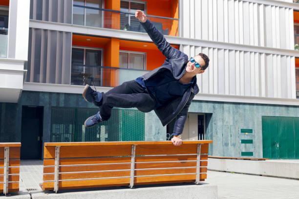 schönen jungen mann eine bank in der straße springen. - parkour stock-fotos und bilder