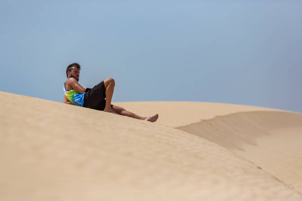 A young handsome man laying down on the sand of the dunes in a beach of Fuerteventura stock photo