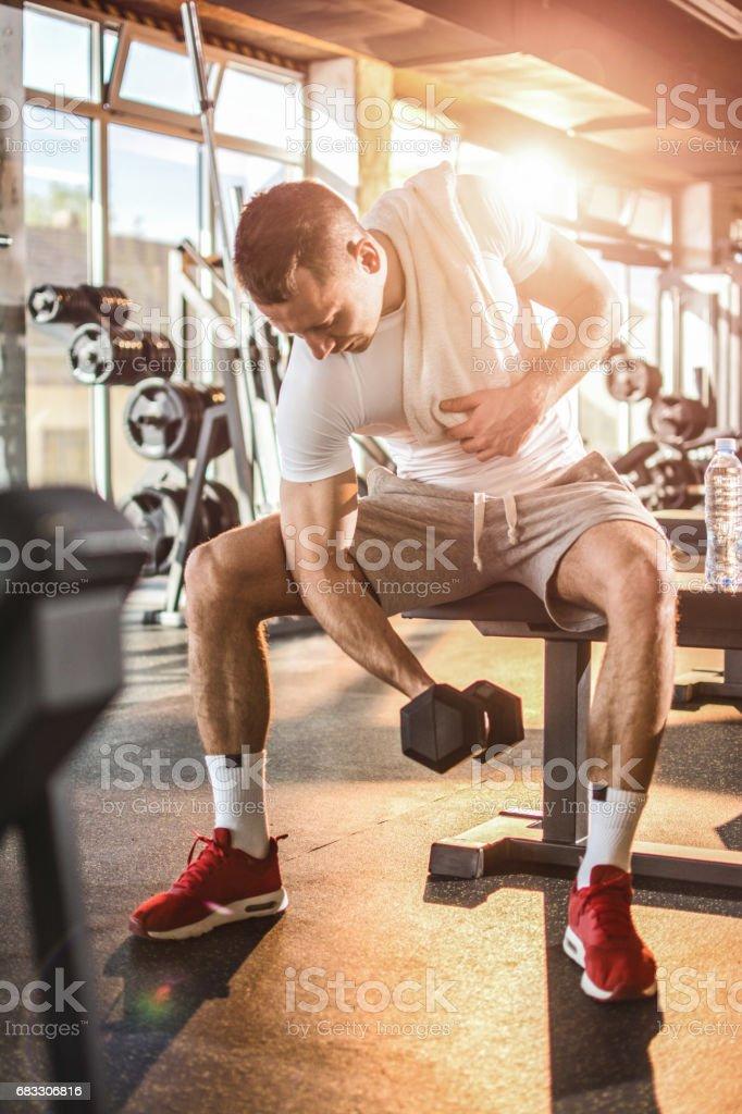 Young handsome man lifting weights in gym. royaltyfri bildbanksbilder