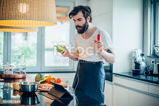 istock Young handsome man listening music and cooking healthy avocado meal 694982948