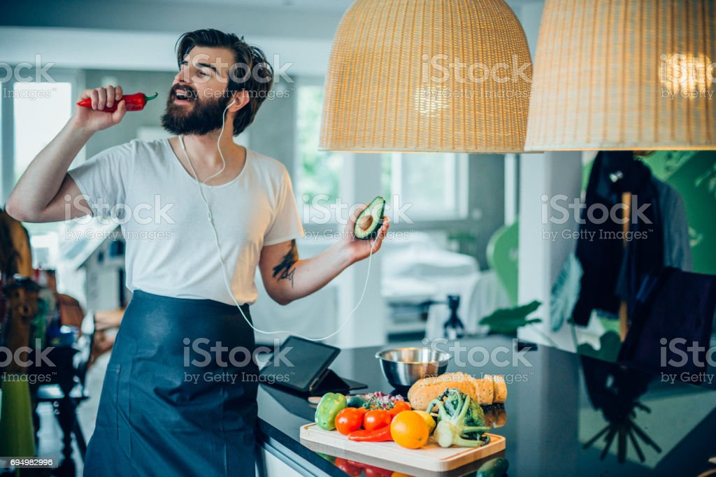 Young handsome man listening music and cooking healthy avocado meal stock photo