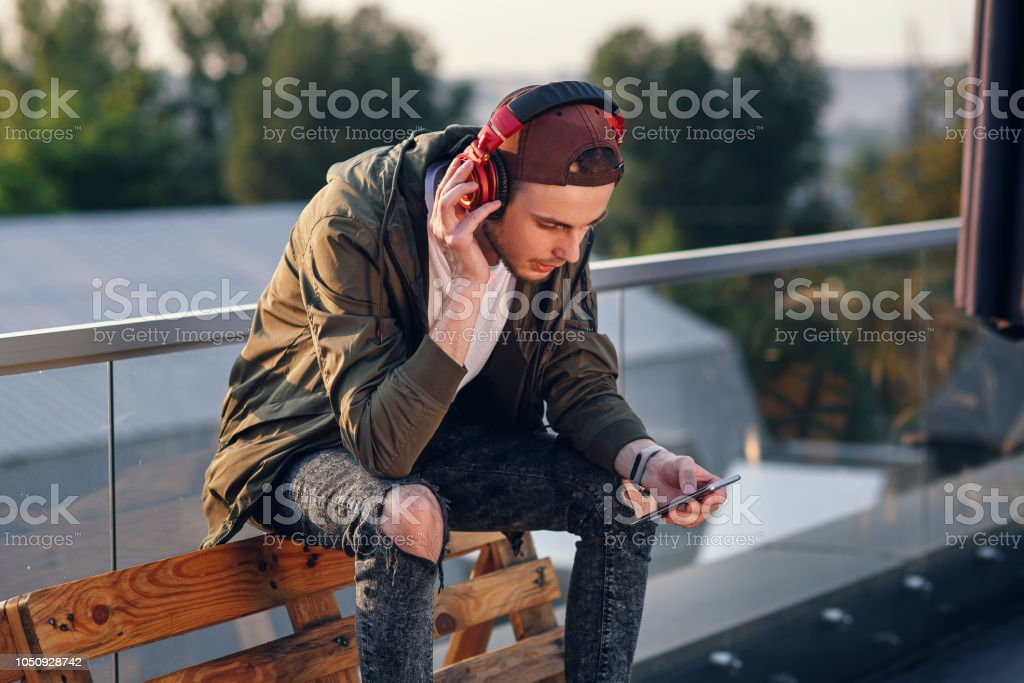 Young handsome man listening music in headphones and using smartphone...