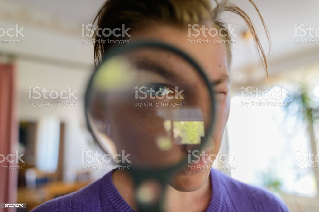 Young handsome man looking through magnifying glass at home stock photo