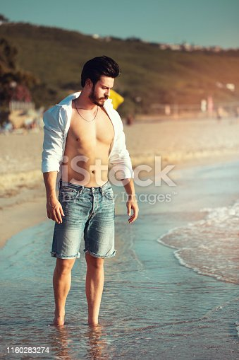 young handsome man on the beach in summer season