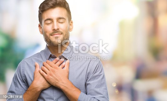 istock Young handsome man over isolated background smiling with hands on chest with closed eyes and grateful gesture on face. Health concept. 1042811916