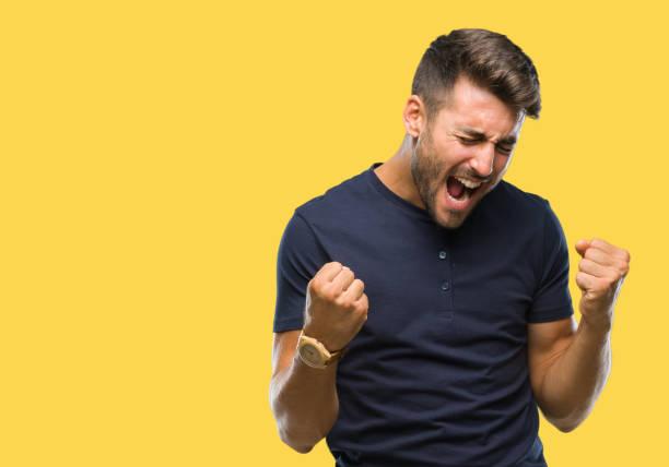 jonge knappe man over geïsoleerde achtergrond erg blij en opgewonden doet winnaar gebaar met armen naar voren gebracht, lachen en schreeuwen voor succes. viering concept. - roepen stockfoto's en -beelden