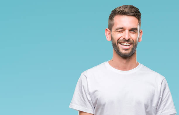 Young handsome man over isolated background winking looking at the camera with sexy expression, cheerful and happy face. stock photo
