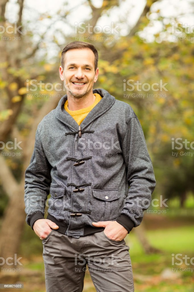 Young handsome man posing in park stock photo