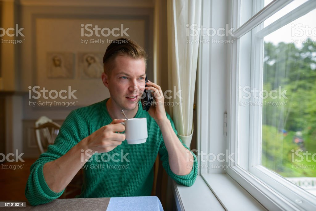 Young handsome man relaxing by the window at home stock photo