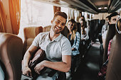 Young Handsome Man Relaxing in Seat of Tour Bus. Attractive Smiling Man Sitting on Passenger Seat of Tourist Bus and Holding Backpack. Traveling and Tourism Concept. Happy Travelers on Trip